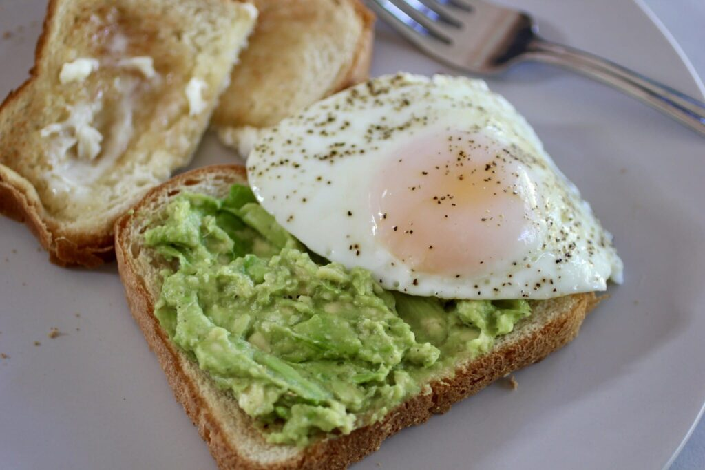 Avocado Toast with sunny side up egg on a plate with a fork