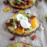 one potato bite on parchment paper with bacon, cheese and sour cream