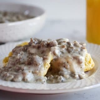 biscuits with gravy on plate with orange juice