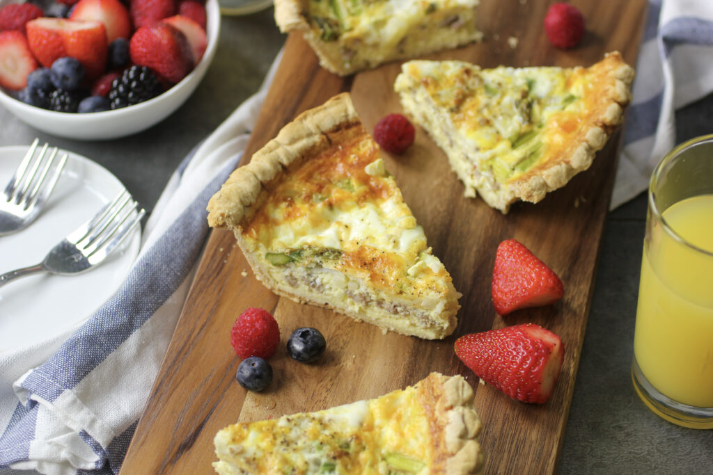 asparagus sausage quiche on cutting board with fruit, juice and plates with forks.