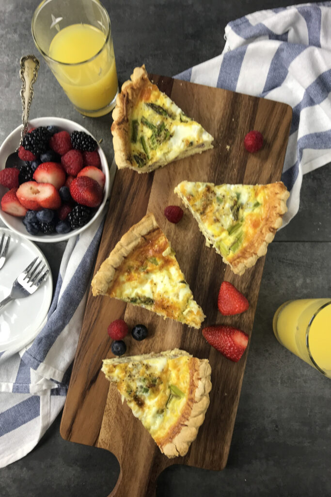 asparagus sausage quiche on a cutting board with fruit and two glasses of orange juice