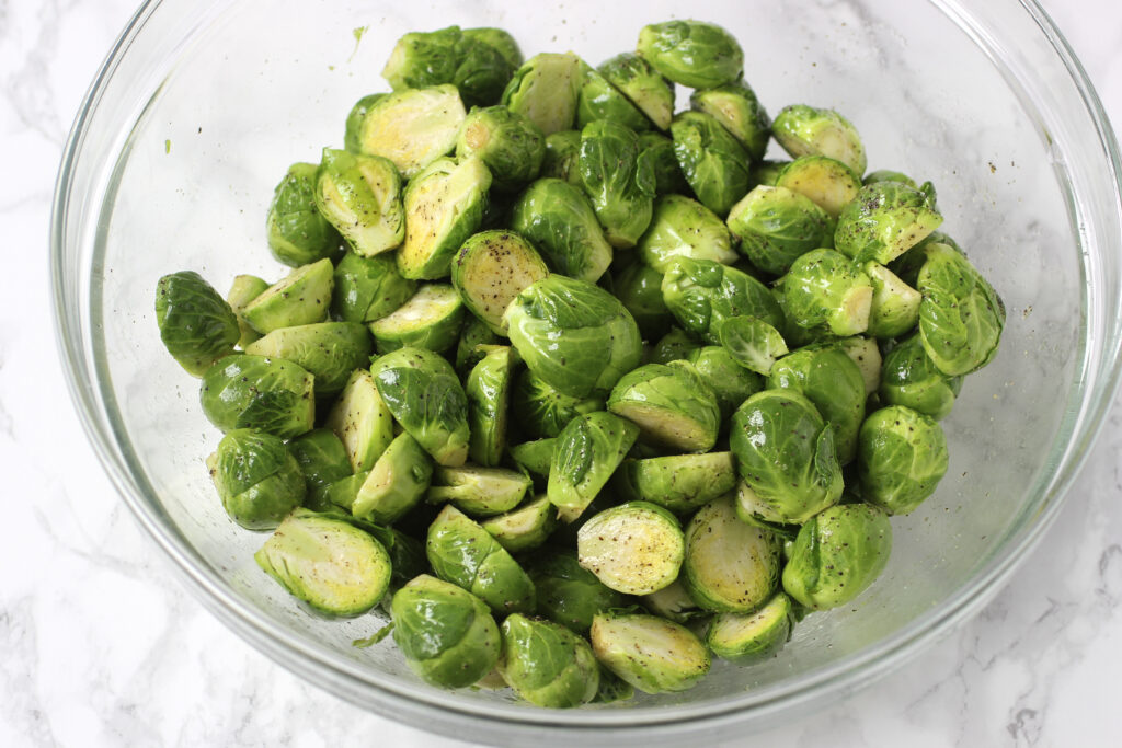 bowl of brussels sprouts with salt, pepper and olive oil
