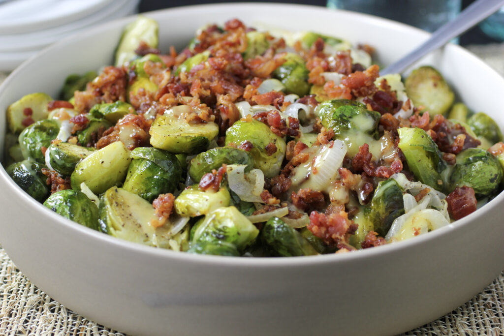 Oven roasted brussels sprouts with onion, bacon and dijon mustard dressing in bowl with serving spoon.