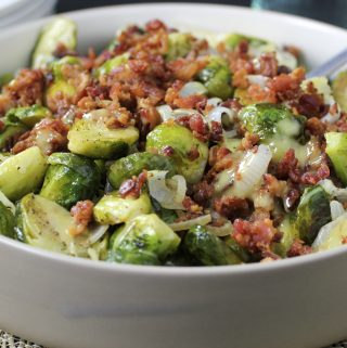 roasted brussels sprouts with bacon, onion and dijon dressing in bowl with spoon