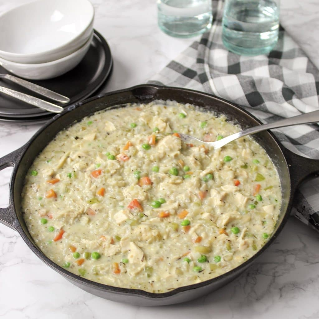 low carb chicken pot pie in iron skillet on table with bowls and cups