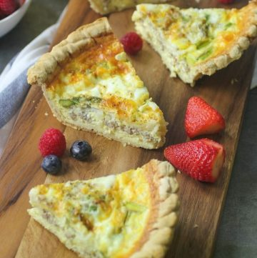 three pieces of quiche on cutting board with fruit