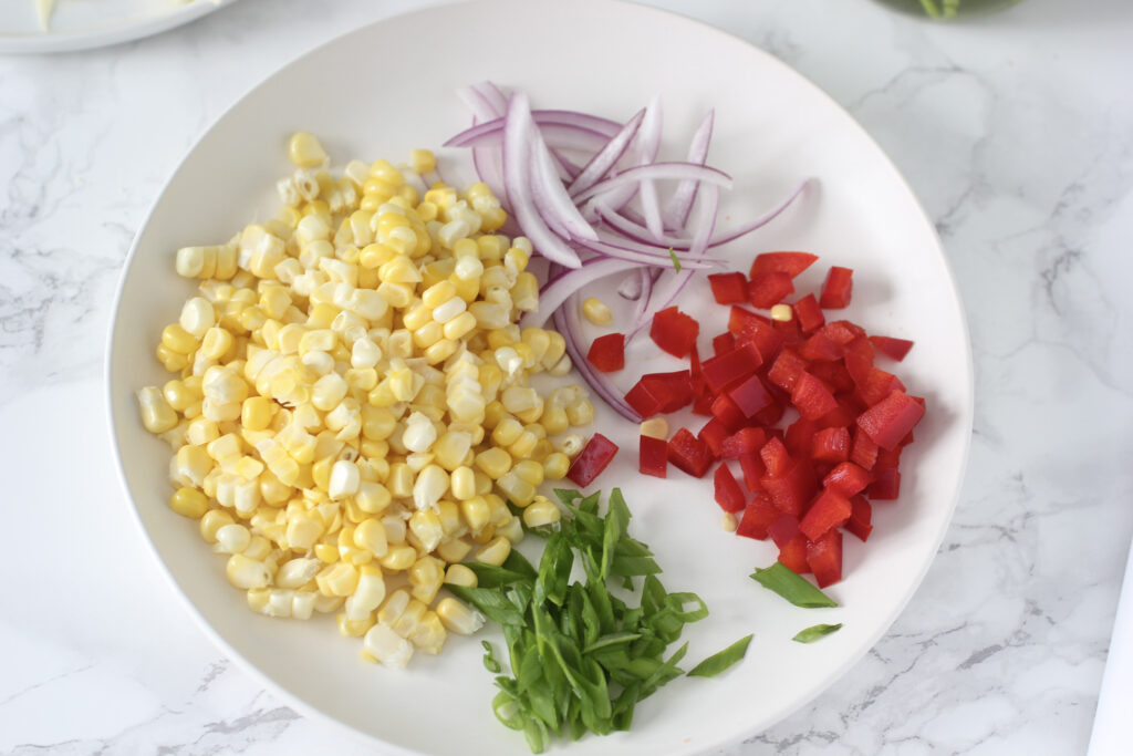 corn cut from cob, green onions, diced red bell pepper, sliced red onion on place