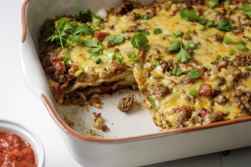 cream cheese beef enchilada casserole in casserole dish with one piece missing and a small side bowl of salsa