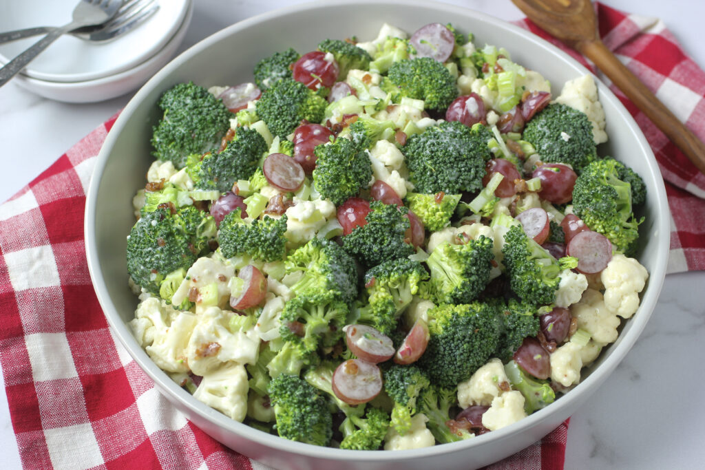 Broccoli Cauliflower Salad with Bacon in bowl with serving spoon and two plates and two forks with napkin