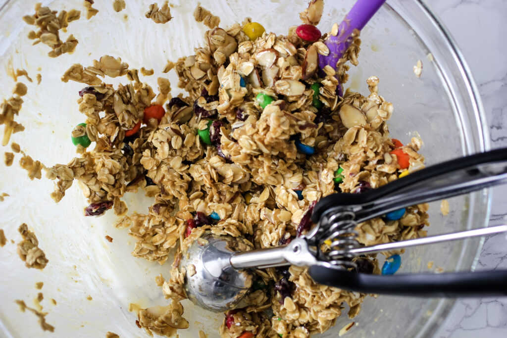 granola bites in mixing bowl with cooking scoop and spatula