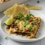 cream cheese enchilada casserole on plate with lime and chips