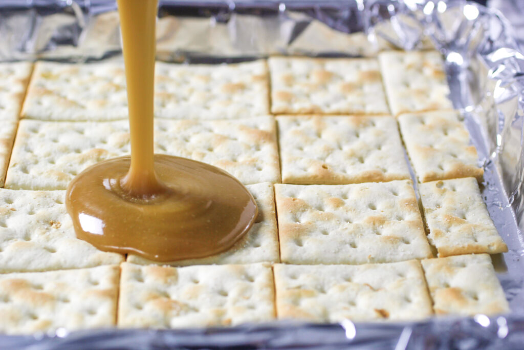 saltine crackers on foil with toffee pouring on to the crackers