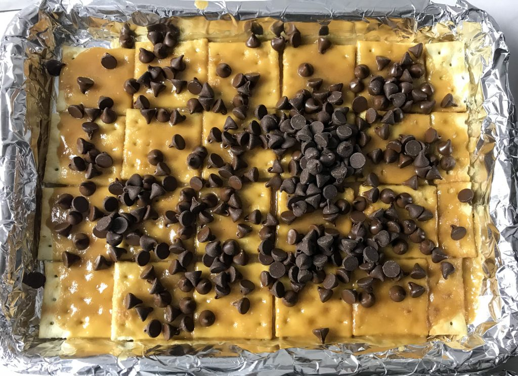 saltine crackers with toffee and chocolate chips on foil lined cookie sheet