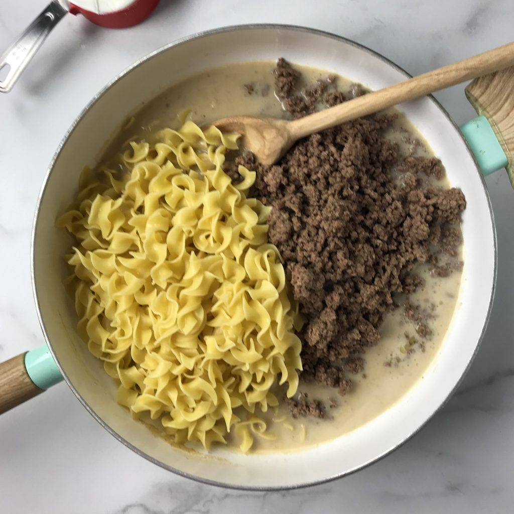 sauce, ground beef and noodles in a skillet