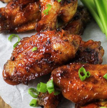 honey bourbon chicken wings on plate with celery and green onions