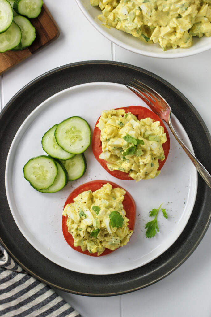 curried egg salad on plate with sliced tomatoes and cucumbers