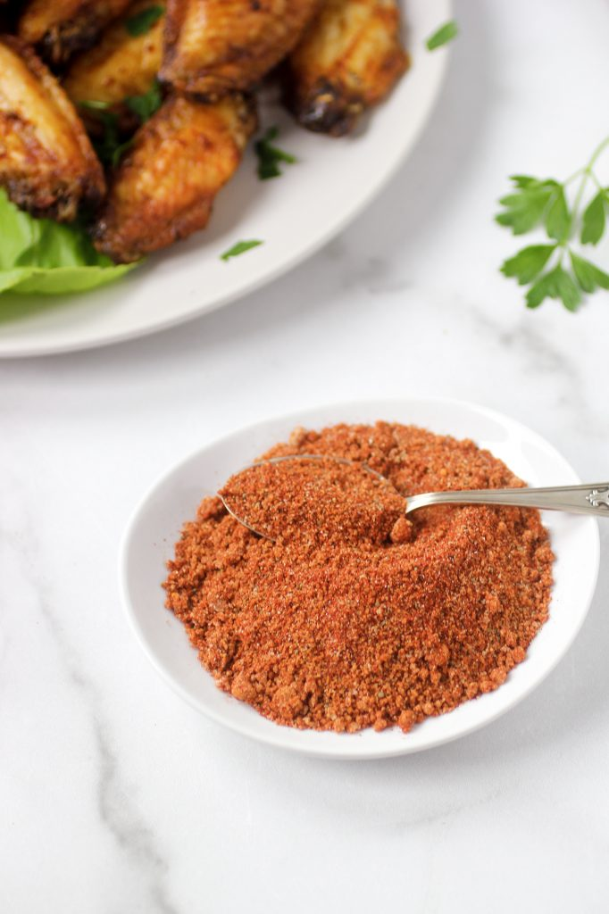 bbq spice rub in bowl with spoon and wings in the back ground