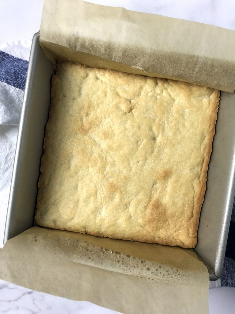 cooked shortbread in the bottom of a pan with parchment paper.