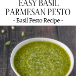 bowl of pesto on wooden table with pine nuts and fresh basil sprinkled on around