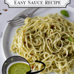 pesto basil pasta on plate with fork and basil leaves. Bowl of basil pesto on side