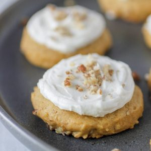 two pumpkin pecan cookies iced with butter cream and sprinkled with pecans on a gray plate