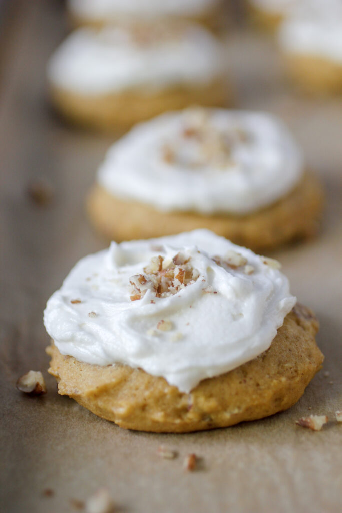 pumpkin pecan cookies with icing and nuts on cookie sheet