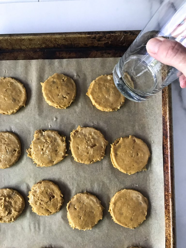 raw pumpkin pecan cookie dough on parchment paper with a glass for flattening cookies