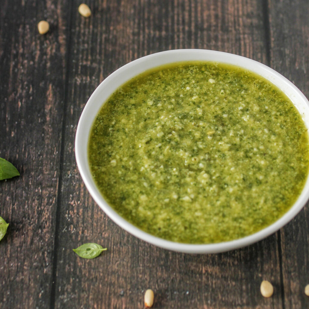 small bowl of Fresh Basil Parmesan Pesto on wood table with pine nuts sprinkled around.