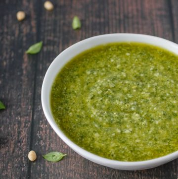white bowl of pesto on wood table with sprinkles of pine nuts and fresh basil