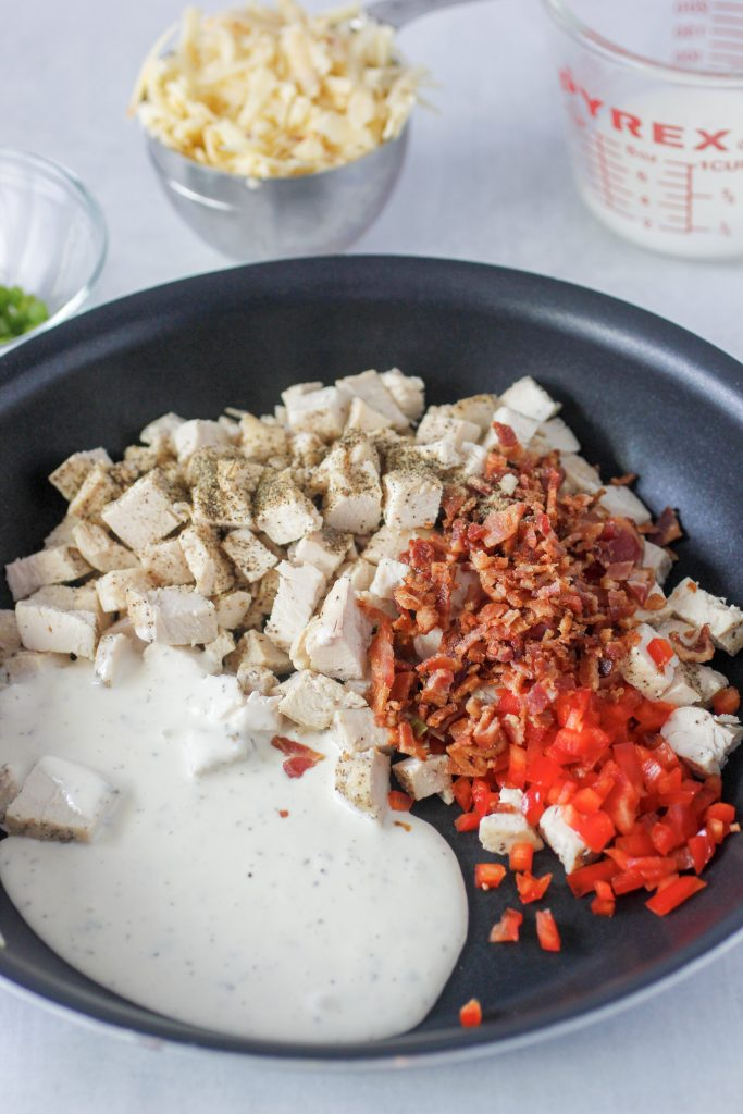 skillet with diced cooked chicken, bacon, ranch dressing and red bell peppers.