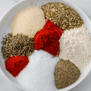 eight different spices on a plate that will make cajun seasoning