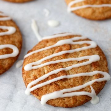 cinnamon sugar coated cookie with icing drizzled over the top on parchment paper with other cookies