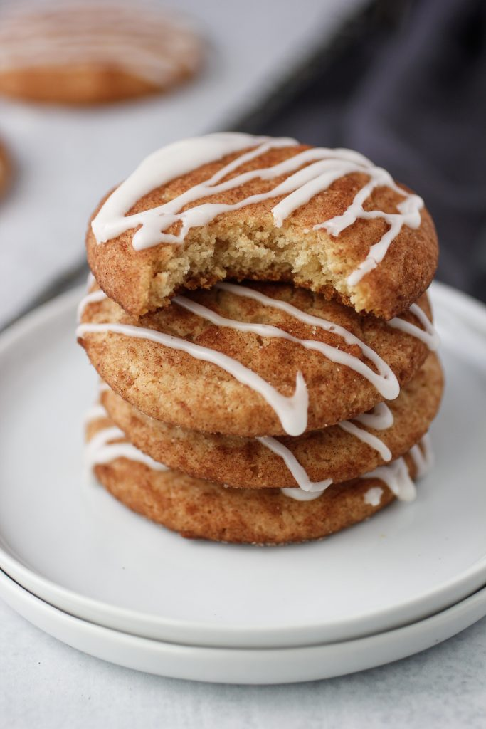 three cinnamon roll cookies stacked on a plate with the fourth cook having a bite out of it