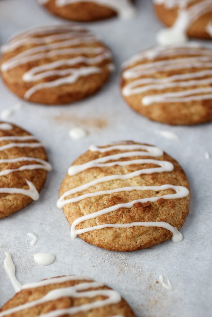 cinnamon roll cookies on cookie sheet with parchment paper