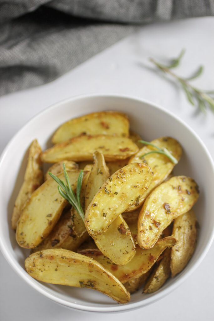 rosemary fingerling potatoes in a bowl with a sprig of fresh rosemary