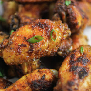 cajun wings that have been cooked with a cajun spice rub and are garnished with green onions
