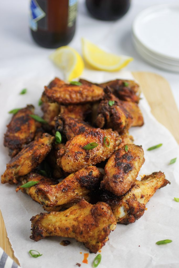 Cajun chicken wings on parchment paper with green onions and lemon wedges