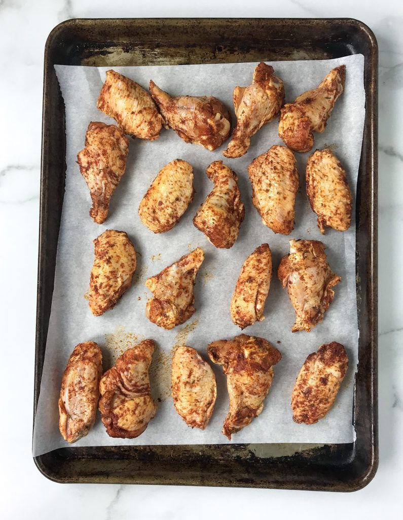 chicken wings with Cajun spice blend on parchment paper on baking sheet ready for the oven