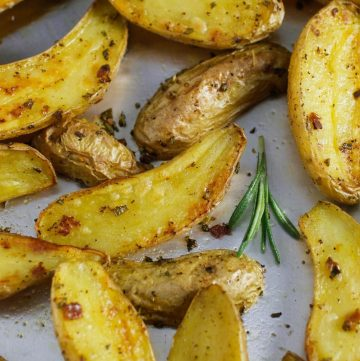 rosemary potatoes on sheet pan with sprig of rosemary