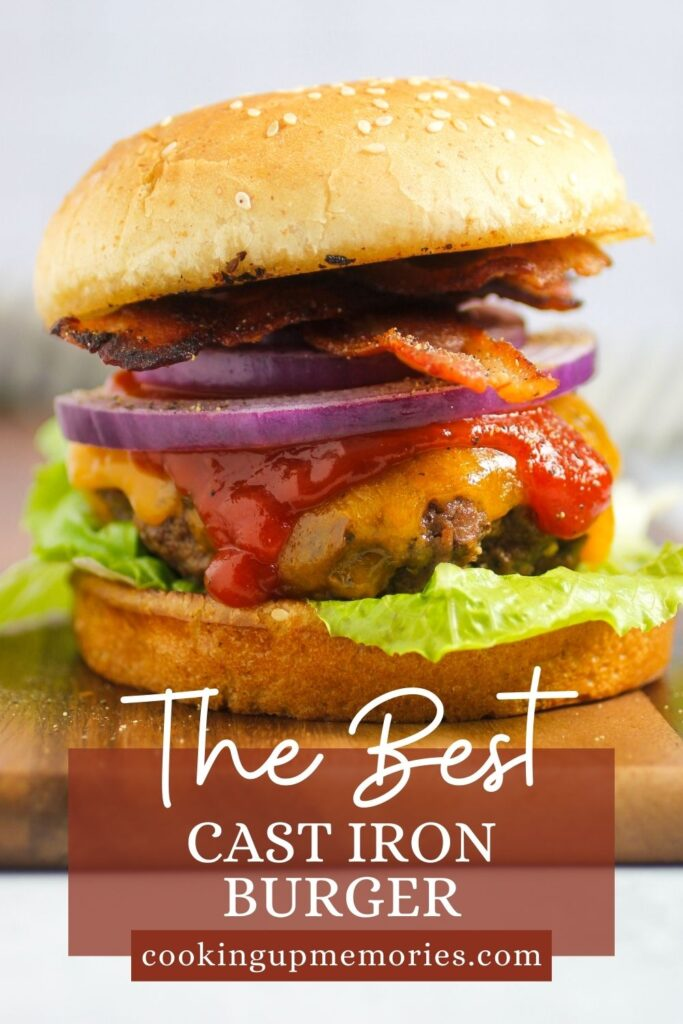 cast iron burger with onion, ketchup, lettuce, bacon on toasted bun on a cutting board