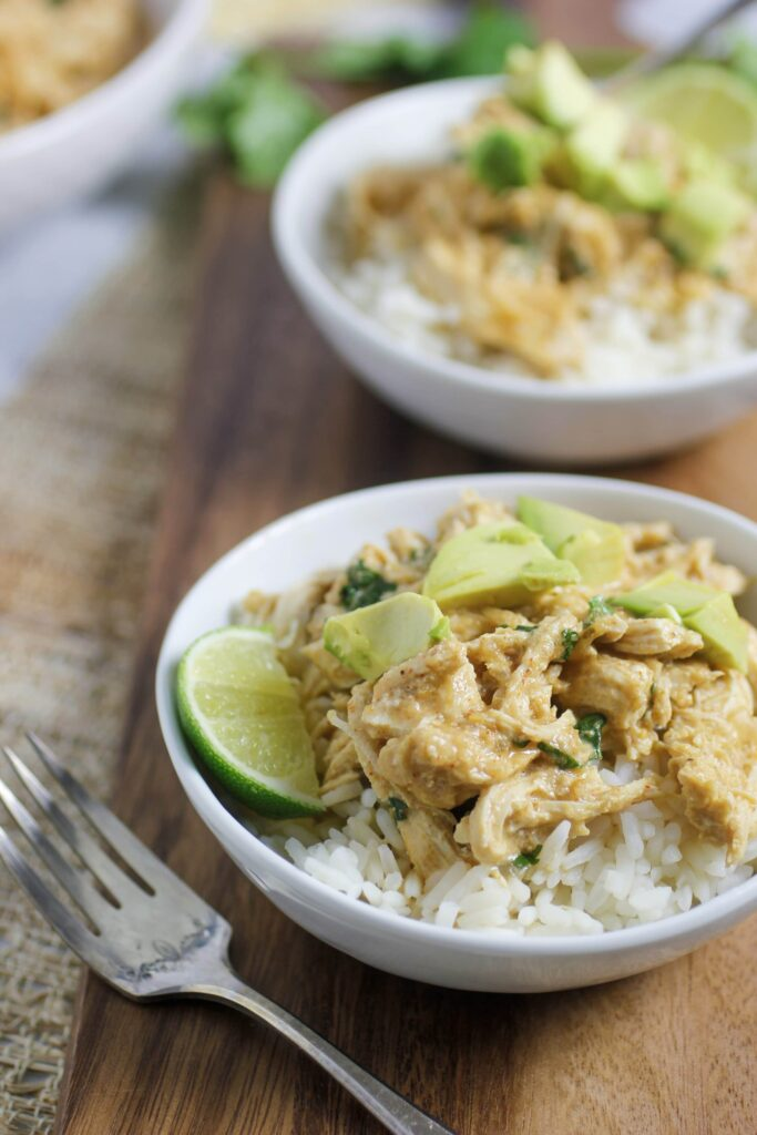two bowls of salsa verde chicken over rice on a cutting bowl with cilantro and two spoons