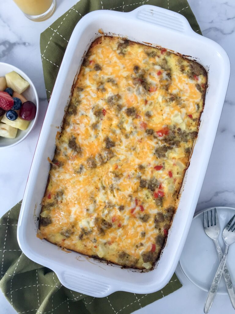 cheesy breakfast casserole in casserole dish right out of the oven with fruilt and plates