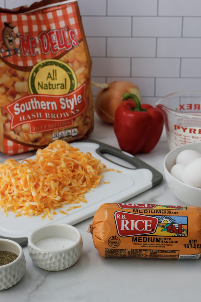 The ingredients to make Cheesy Hashbrown Breakfast Casserole - bag of hashbrowns, red bell pepper, yellow onion, shredded cheese on cutting board, salt and pepper with a measuring cup with that has milk