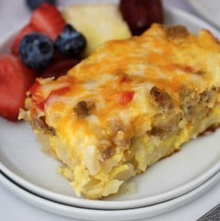 one slice of cheesy hashbrown breakfast casserole on white plate with mixed fruit