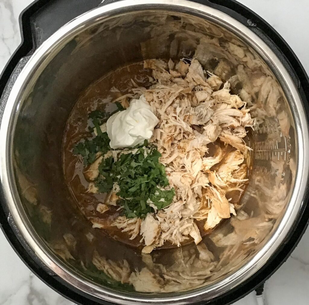 shredded chicken, salsa verde sauce with spices, sour cream and cilantro in an instant pot