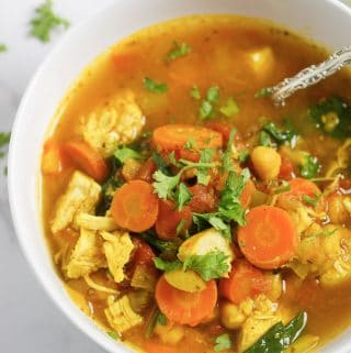 Tuscan Soup with carrots, chicken, celery, chickpeas in a flavorful sauce in a white bowl garnished with fresh parsley