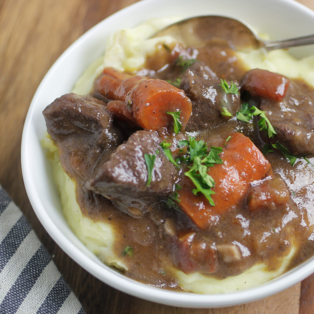 red wine beef stew over mashed potatoes with parsley sprinkled on top