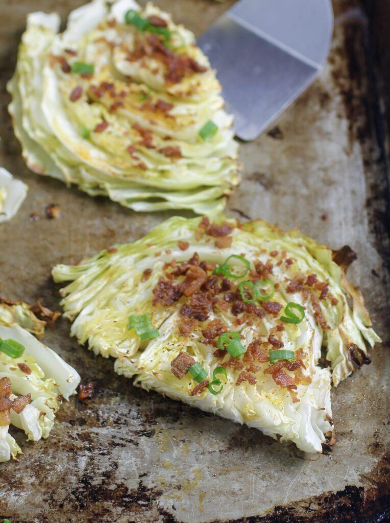 Roasted Cabbage with bacon, spices and green onions on baking sheet