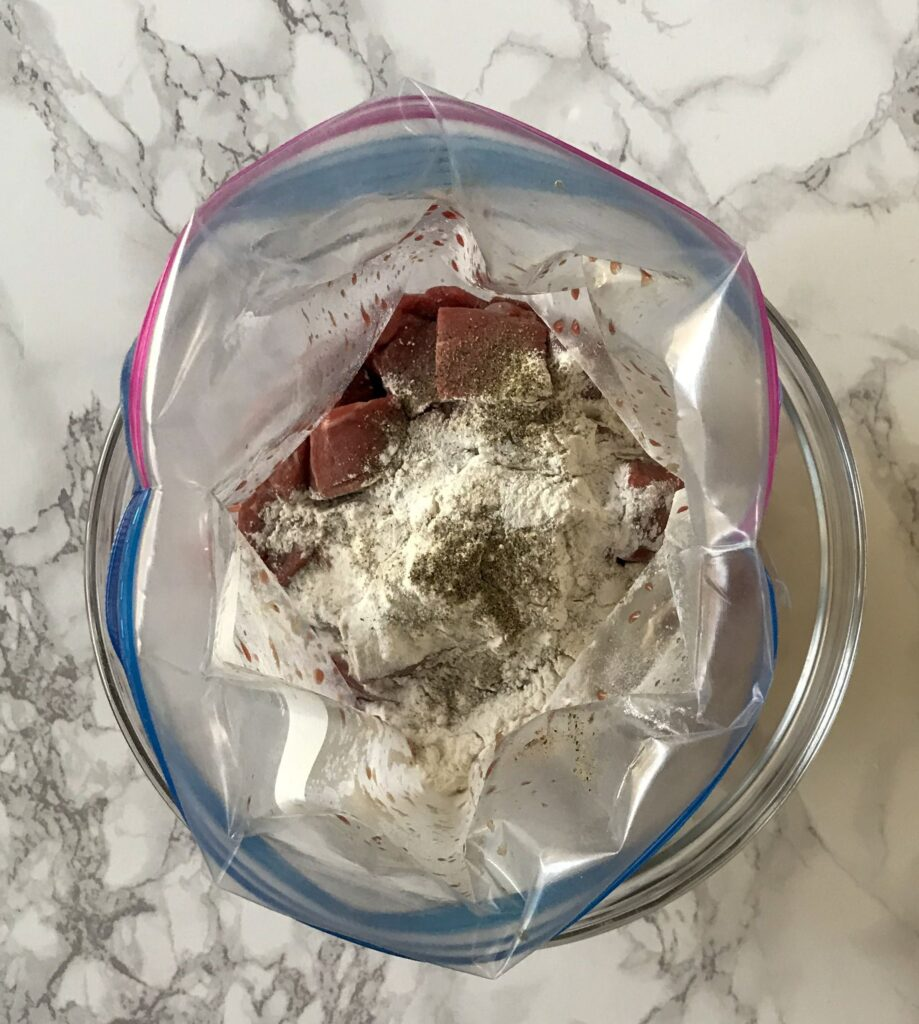 stew meat in a ziplock with flour, salt and pepper
