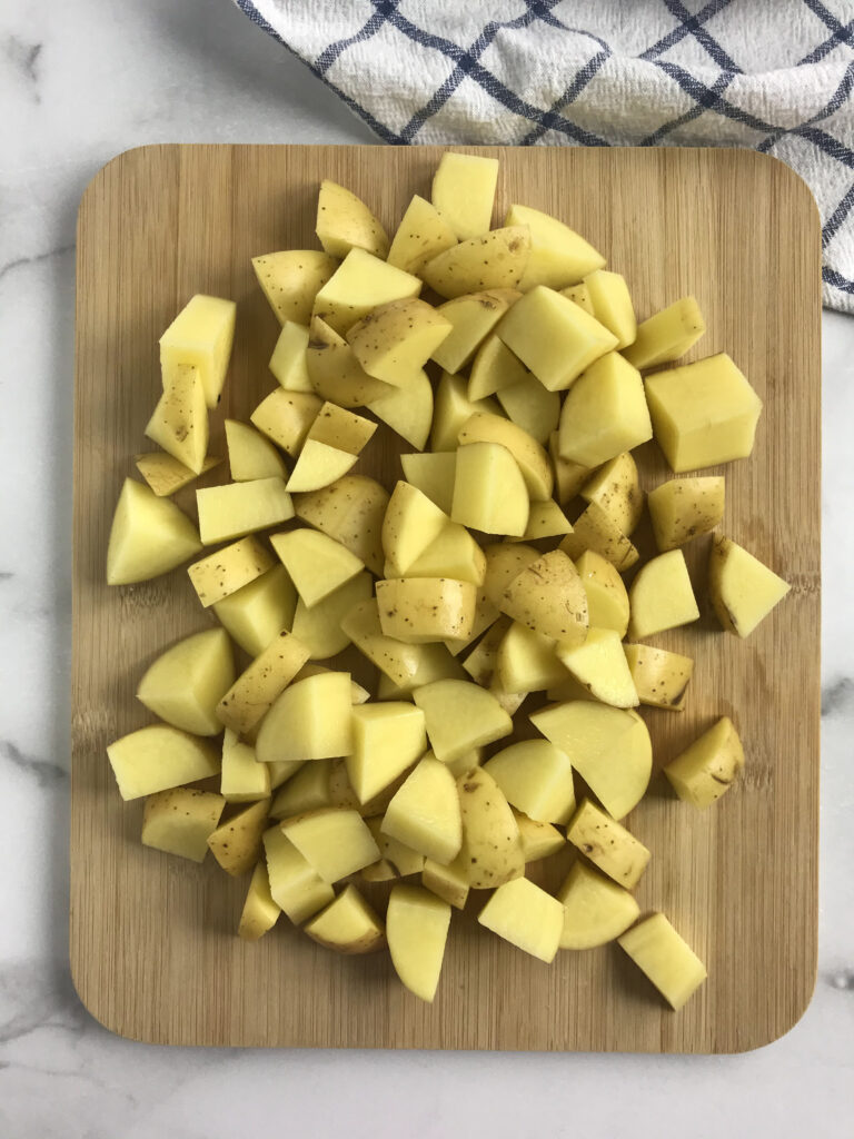 Diced Potatoes on cutting board with kitchen towel